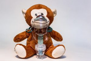 Stuffed monkey wearing an inhalation mask used in COPD treatments