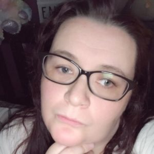 image is a photo of a caucasian woman with dark hair, wearing glasses and looking of to the bottom right of the image